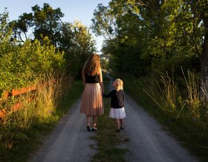 Mother and daughter walking down path
